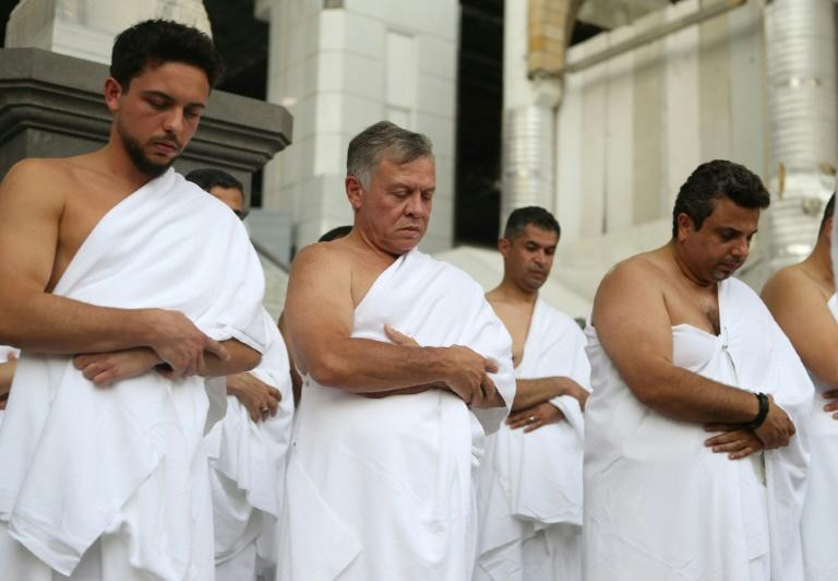 Jordan's King Abdullah II (C) and his son Crown Prince Hussein bin Abdullah (L) perform the off-season pilgrimage of Umra in the holy city of Mecca in June 2018