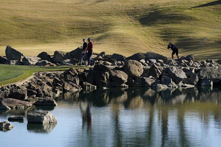 Professional golfers walk past a water feature at the Pete Dye Stadium Course on PGA West in La Quinta in January.