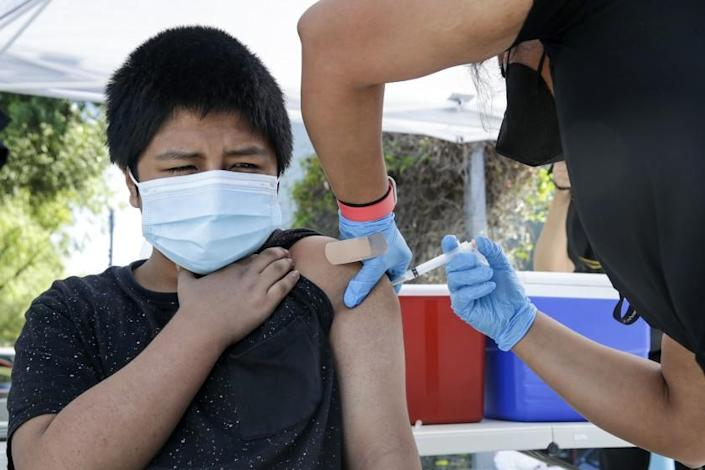 Los Angeles, CA - June 24: Diego Lavin, 12, left, gets a COVID19 vaccine at mobile clinic held at Los Angeles City Councilman Curren Price's district office. After getting vaccine Lavin got a free pair of ``Beats by Dre'' headphones at Councilman Curren Price's district office on Thursday, June 24, 2021 in Los Angeles, CA. (Irfan Khan / Los Angeles Times)