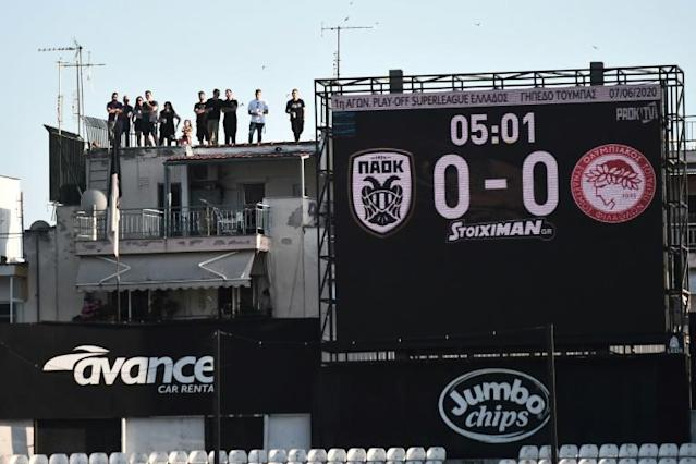 Roof dwellers: PAOK fans watch the Greek Super League game against Olympiakos above the Toumba stadium in Thessaloniki (AFP Photo/Sakis MITROLIDIS)