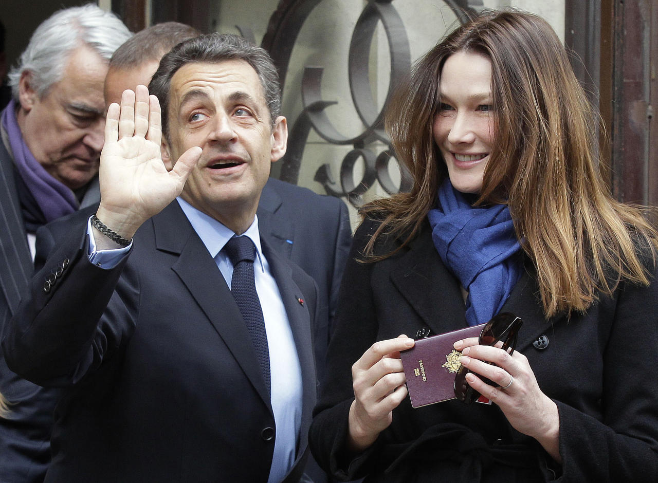 French President and UMP candidate Nicolas Sarkozy and his wife Carla Bruni-Sarkozy leave after casting their votes in the first round of French presidential elections in Paris, France, Sunday, April 22, 2012. (AP Photo/Michel Euler)