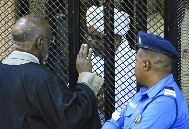 Sudan's deposed president Omar al-Bashir sits in a defendant's cage during his corruption trial in Khartoum on December 14