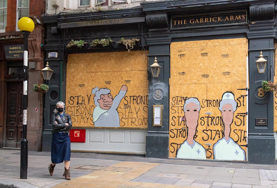 A woman wearing a protective face mask passes a boarded up pub painted with a 'stay strong' mural, in central London, as further coronavirus lockdown restrictions are lifted in England. (Photo by Dominic Lipinski/PA Images via Getty Images)