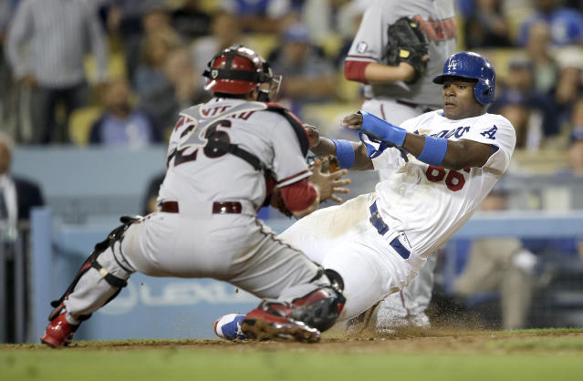 Los Angeles Dodgers' Yasiel Puig, right, tries to score on a single hit by Scott Van Slyke as Arizona Diamondbacks catcher Miguel Montero applies a tag during the eighth inning a baseball game on Monday, Sept. 9, 2013, in Los Angeles. (AP Photo/Jae C. Hong)