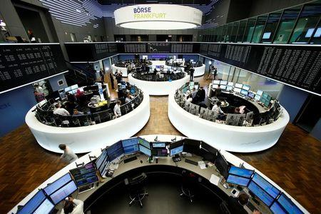 Traders work at their desks in front of the German share price index DAX board in Frankfurt