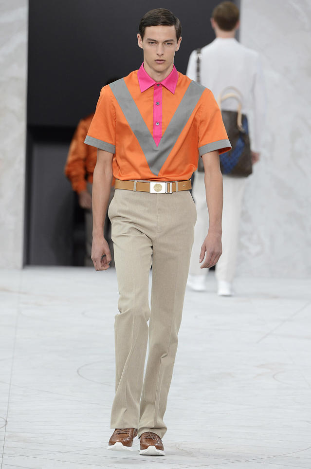 <p>Model wears a bright-contrast orange, pink, and gray polo shirt with beige trousers, brown sneakers, and matching belt. (Photo: Catwalking) </p>