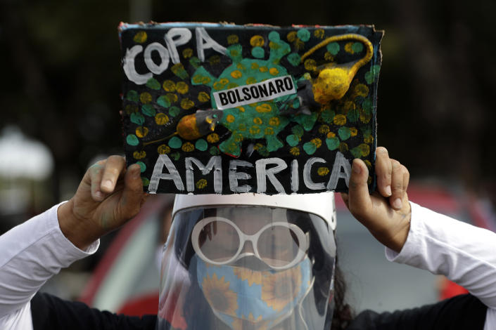 A woman holds a sign to protest against Brazil holding the Copa America in Brasilia, Brazil, Sunday, June 6, 2021. Brazil accepted hosting the South American soccer tournament after the original co-hosts were dropped, Colombia due to political protests and Argentina for rising of COVID-19 cases. (AP Photo/Eraldo Peres)