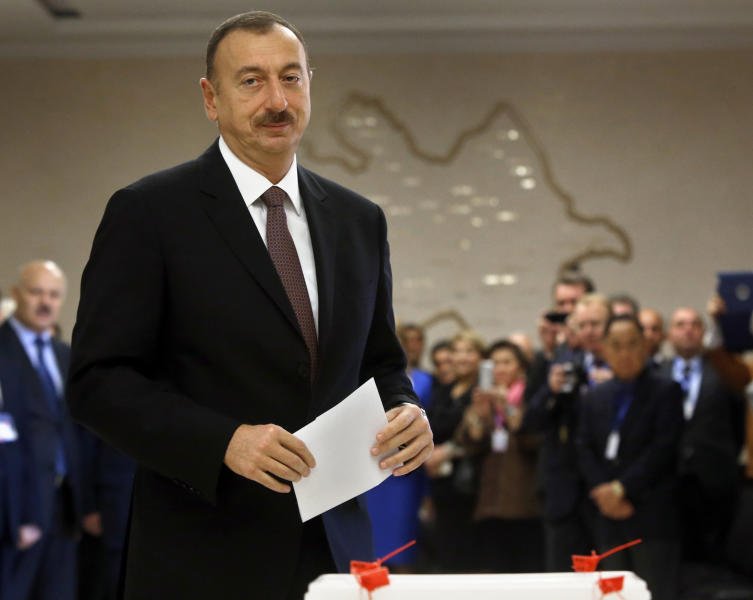 Azerbaijan President Ilham Aliyev prepares to cast his ballot paper during the voting at a polling station in Baku, Azerbaijan, Wednesday, Oct. 9, 2013. Oil-rich Azerbaijan is booming and the wealth is trickling down to its poorest people. It all means that its president doesn't even need to clamp down too hard to ensure he extends a decades-long dynastic rule in elections on Wednesday. (AP Photo/Sergei Grits)
