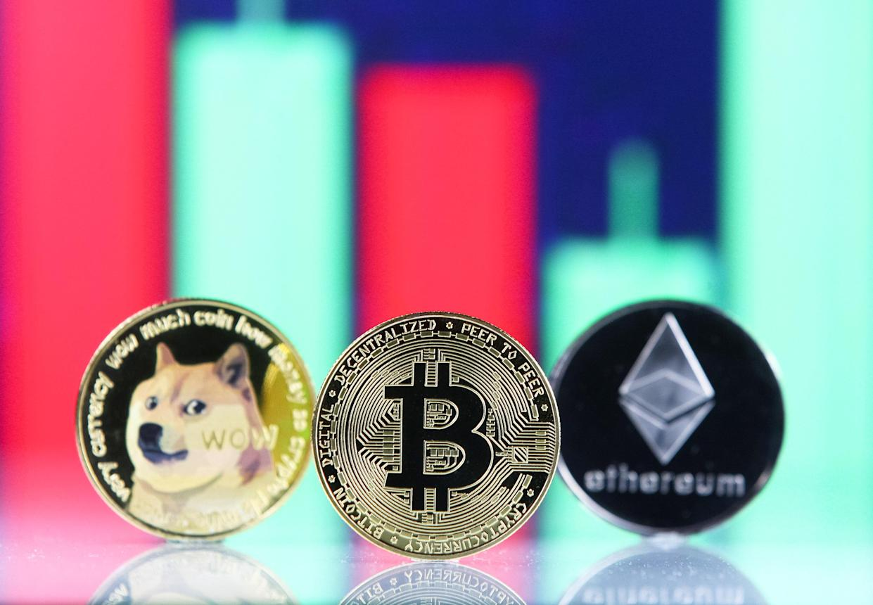 Bitcoin, Dogecoin, Ethereum cryptocurrency coins and a graph are pictured in Kyiv on 08 July, 2021. (Photo by STR/NurPhoto via Getty Images)