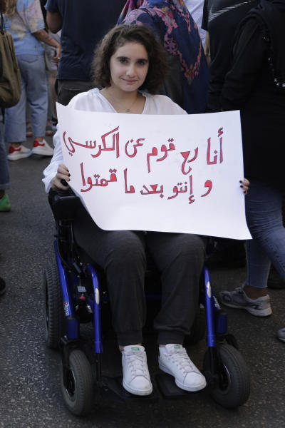 """An anti-government protester in a wheelchair holds a banner that reads in Arabic """"I will get out from my chair, before you do,"""" during a protest in Beirut, Lebanon, Tuesday, Oct. 22, 2019. Prime Minister Saad Hariri briefed western and Arab ambassadors Tuesday of a reform plan approved by the Cabinet that Lebanon hopes would increase foreign investments to help its struggling economy amid wide skepticism by the public who continued in their protests for the sixth day. (AP Photo/Hassan Ammar)"""