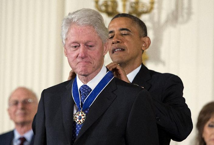 President Barack Obama awards former President Bill Clinton with the Presidential Medal of Freedom, Wednesday, Nov. 20, 2013, during a ceremony in the East Room of the White House in Washington. (AP Photo/ Evan Vucci)