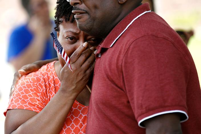 Patricia Olds, a coworker of LaQuita Brown, a victim of a mass shooting at a municipal building in Virginia Beach, Va., is comforted before carrying a cross bearing Brown's name to a nearby makeshift memorial, June 2, 2019. (Photo: Patrick Semansky/AP)