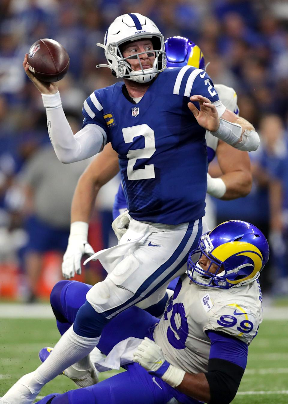 Indianapolis Colts quarterback Carson Wentz (2) tries to pass as he's brought down by Los Angeles Rams defensive end Aaron Donald (99) on Sunday, Sept. 19, 2021, during a game against the Los Angeles Rams at Lucas Oil Stadium in Indianapolis.