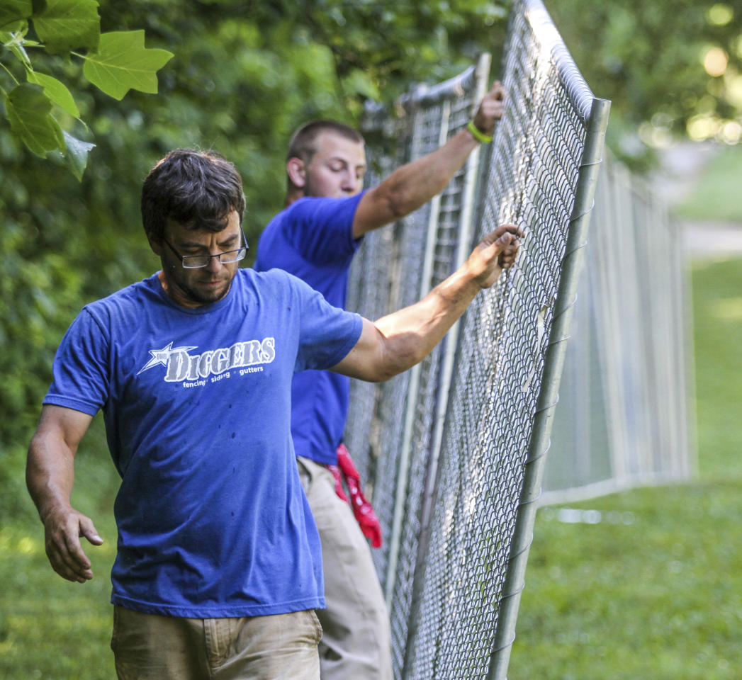 Daniel Jones, foreground, and Hugh Brooks, both with Digger's Fencing, set up fencing in the Lambert Pioneer Village area of at Yellow Creek Park on Monday, June 19, 2017, in Owensboro, Ky. The two are part of a crew with Digger's Fencing that is erecting more than 7,000 feet of fencing at the park for ROMP Fest, which begins June 21. (Greg Eans/The Messenger-Inquirer via AP)