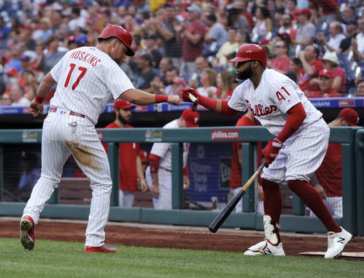 Philadelphia Phillies' Rhys Hoskins (17) celebrates with Carlos Santana (41) after scoring a run on a Nick Williams single during the first inning of a baseball game against the New York Mets, Friday, Aug. 17, 2018, in Philadelphia. (AP Photo/Michael Perez)