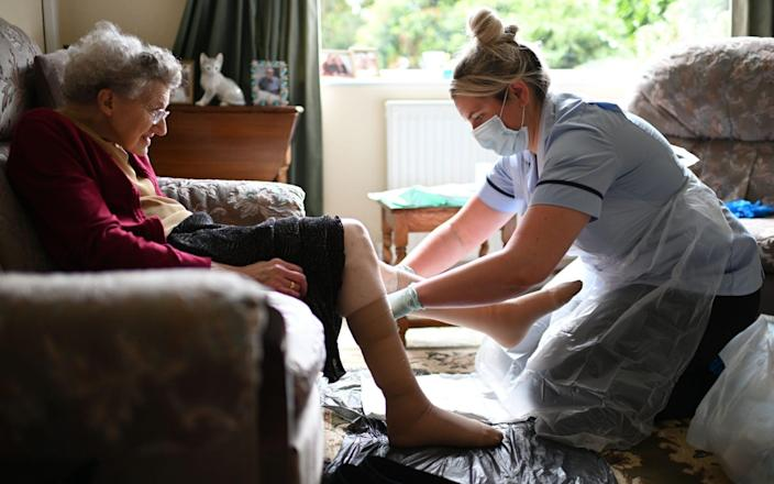 File photo dated 09/06/20 a nurse Rebecca, wearing personal protective equipment (PPE), changes the dressings on the legs of an elderly woman during a home visit. Workers in care homes and other parts of the sector are being forced to take unpaid leave or survive on statutory sick pay (SSP) if they have to self-isolate or have coronavirus, according to their union - PA