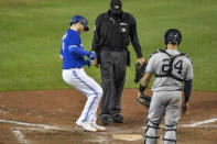 Toronto Blue Jays' Danny Jansen, left, crosses home plate in front of New York Yankees catcher Gary Snchez, right, after hitting a solo home run during the eighth inning of a baseball game in Buffalo, N.Y., Wednesday, Sept. 23, 2020. (AP Photo/Adrian Kraus)