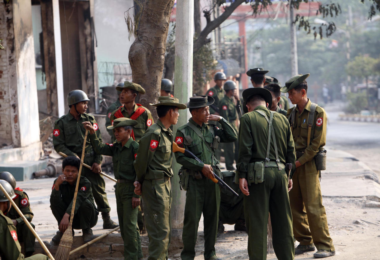 Myanmar soldiers take a break as they remove debris from destroyed buildings and others provide security, following the ethnic unrest between Buddhists and Muslim, in Meikhtila, about 550 kilometers (340 miles) north of Yangon, Myanmar, Monday, March 25, 2013. Sectarian clashes between Buddhists and Muslims in Meikhtila spread to at least two other towns in the country's heartland over the weekend, undermining government efforts to quash an eruption of violence that has killed dozens of people and displaced 10,000 more. On Sunday, Vijay Nambiar, the U.N. secretary-general's special adviser on Myanmar, toured Meikhtila, where soldiers were able to impose order after several days of anarchy and called on the government to punish those responsible. (AP Photo/Khin Maung Win)