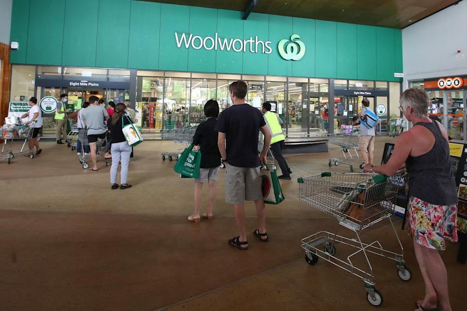 People stand in line outside a Woolworths at a southern suburb of Brisbane. Source: Getty Images