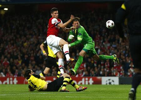 Arsenal's Olivier Giroud (L) challenges Borussia Dortmund's goalkeeper Roman Weidenfeller to score a goal during their Champions League soccer match at the Emirates stadium in London October 22, 2013. REUTERS/Eddie Keogh