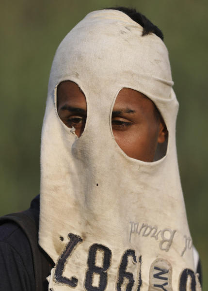 An anti-government Venezuelan migrant uses a T-shirt to mask his face as he rests from confrontations with Venezuelan National Guards who are blocking the Simon Bolivar International Bridge, in La Parada near Cucuta, Colombia, Sunday, Feb. 24, 2019, on the border with Venezuela. A U.S.-backed drive to deliver foreign aid to Venezuela on Saturday met strong resistance as troops loyal to President Nicolas Maduro blocked the convoys at the border and fired tear gas on protesters. (AP Photo/Fernando Vergara)