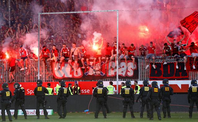 Soccer Football - 2. Bundesliga - SV Sandhausen v Nuremberg - BWT-Stadion am Hardtwald, Sandhausen, Germany - May 6, 2018 Nuremberg fans with flares as police look on REUTERS/Kai Pfaffenbach DFL RULES TO LIMIT THE ONLINE USAGE DURING MATCH TIME TO 15 PICTURES PER GAME. IMAGE SEQUENCES TO SIMULATE VIDEO IS NOT ALLOWED AT ANY TIME. FOR FURTHER QUERIES PLEASE CONTACT DFL DIRECTLY AT + 49 69 650050