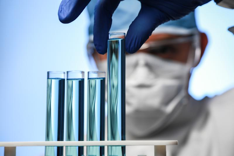 Scientist picking up a test tube from a rack with three other test tubes in it.