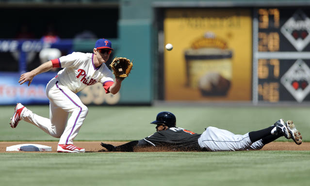 Miami Marlins' Juan Pierre, right, steals second base in front of Philadelphia Phillies' Chase Utley in the first inning of a baseball game on Sunday, May 5, 2013, in Philadelphia. (AP Photo/Michael Perez)