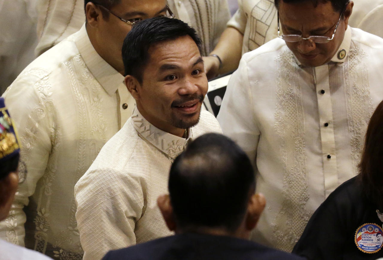 Philippine Senator and boxing hero Manny Pacquiao smiles as he arrives to attend the State of the Nation Address of Philippine President Rodrigo Duterte in suburban Quezon city, north of Manila, Philippines on Monday July 24, 2017. (AP Photo/Aaron Favila)