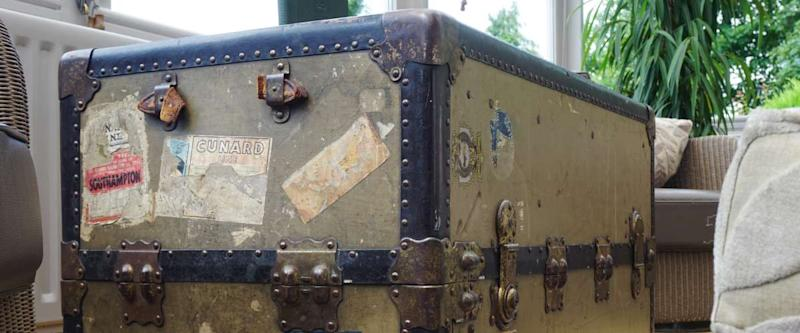 An old trunk travel bag with vintage stickers now serves as a decorative table in an English house