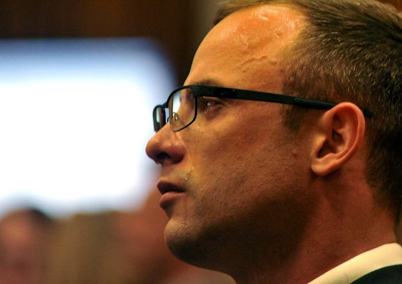 Oscar Pistorius cries as he listens to evidence being given in court in Pretoria, South Africa, Monday, March 24, 2014. Pistorius is on trial for the shooting death of his girlfriend Steenkamp on Valentine's Day 2013. (AP Photo/Ihsaan Haffejee, Pool)
