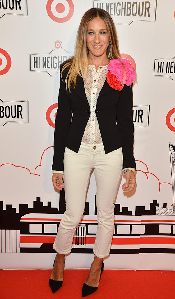 "Carrie Bradshaw reincarnated! On Wednesday, fashion icon Sarah Jessica Parker hit the red carpet for a star-studded Target store opening in Toronto in an ensemble reminiscent of a few outfits once sported by her TV alter ego. The cropped white jeans, black blazer, and pointy heels are signature SJP, but that sheer blouse and floral brooch scream ""Sex and the City!"" (3/27/2013)"