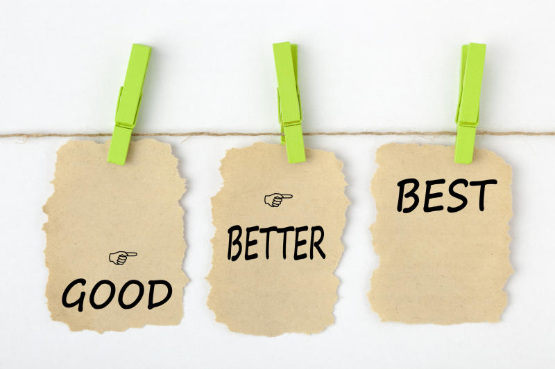 GOOD BETTER BEST writen on old torn paper with clip hanging on white background