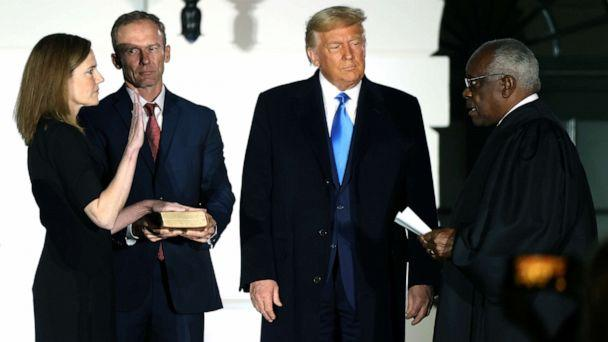 PHOTO: Judge Amy Coney Barrett is sworn in to serve as an associate justice of the Supreme Court by Supreme Court Justice Clarence Thomas as her husband Jesse Barrett and President Donald Trump watch on the South Lawn of the White House, Oct. 26, 2020.    (Jonathan Ernst/Reuters)