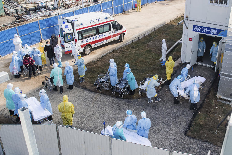 """In this photo released by China's Xinhua News Agency, medical workers in protective suits help transfer the first group of patients into the newly-completed Huoshenshan temporary field hospital in Wuhan in central China's Hubei province. China said Tuesday the number of infections from a new virus surpassed 20,000 as medical workers and patients arrived at a new hospital and President Xi Jinping said """"we have launched a people's war of prevention of the epidemic."""" (Xiao Yijiu/Xinhua via AP)"""