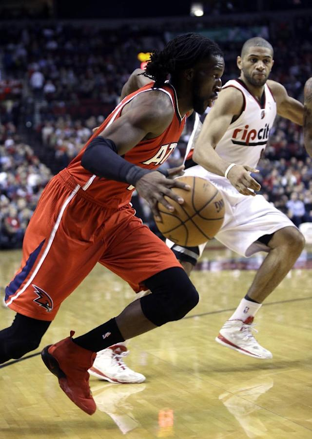Atlanta Hawks forward DeMarre Carroll, left, drives to the basket past Portland Trail Blazers forward Nicolas Batum, from France, during the first half of an NBA basketball game in Portland, Ore., Wednesday, March 5, 2014. (AP Photo/Don Ryan)