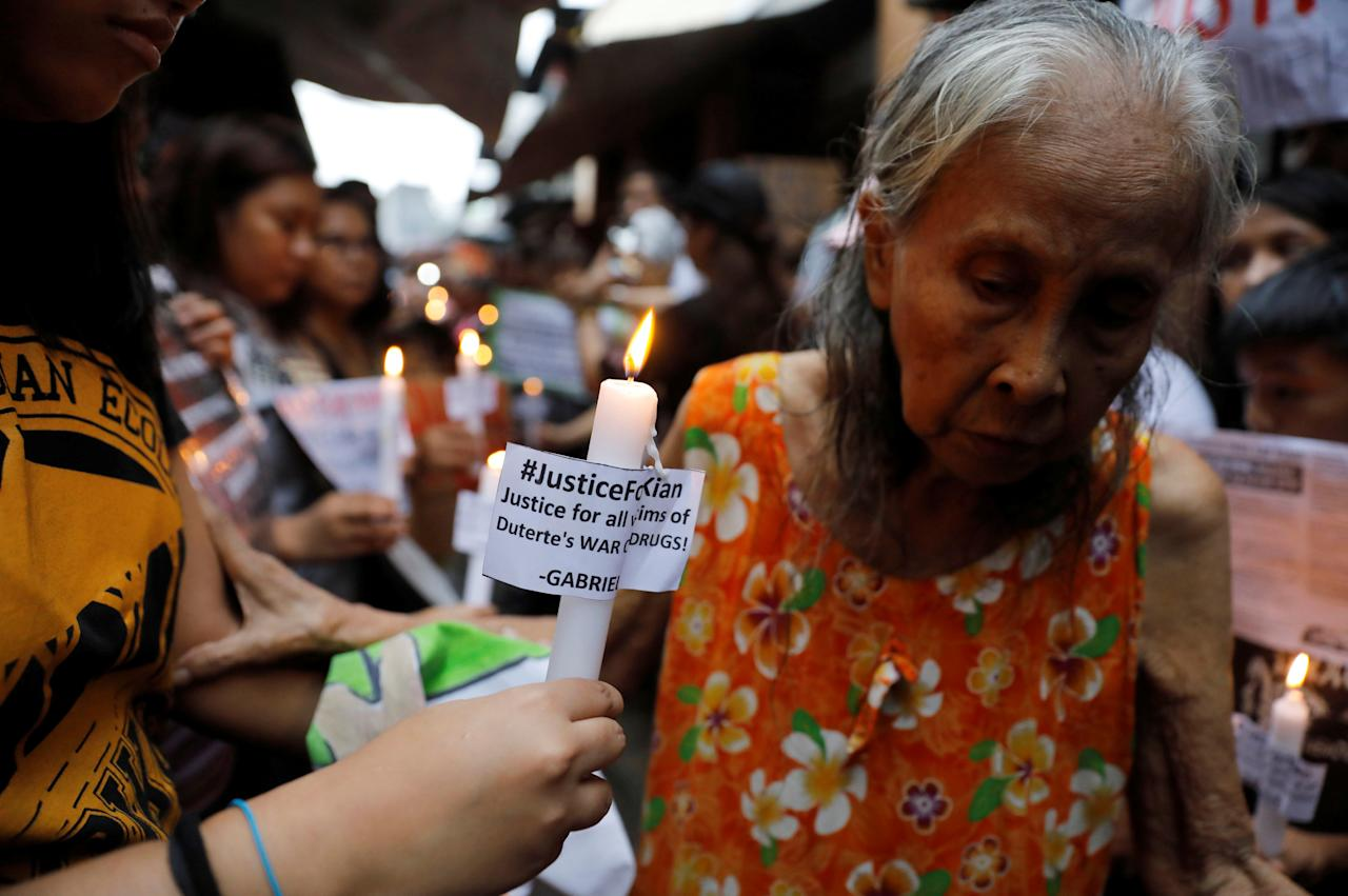Protesters and residents hold lighted candles at the wake of Kian Loyd delos Santos, a 17-year-old high school student, who was among the people shot dead last week in an escalation of President Rodrigo Duterte's war on drugs in Caloocan city, Metro Manila, Philippines August 21, 2017. REUTERS/Erik De Castro