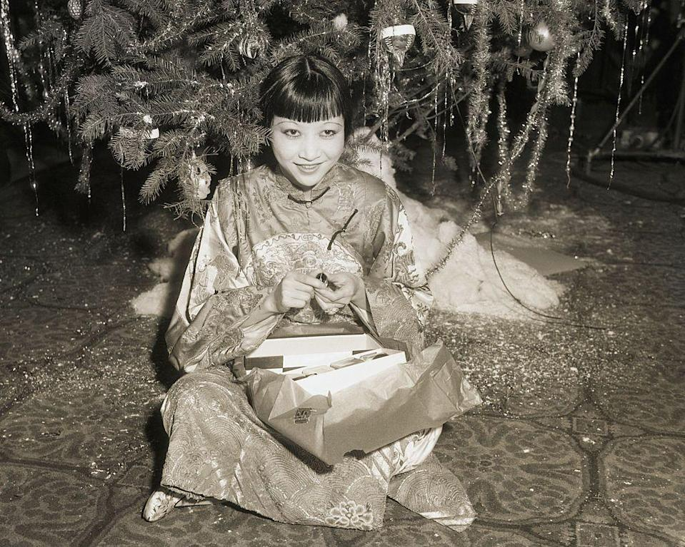 <p>At a Christmas celebration for Hollywood stars at the Christy Hotel in 1932, Anna May Wong opens up a Christmas gift under the tree.</p>