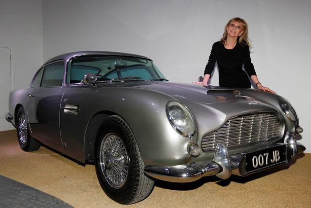 """Actress and former """"Bond Girl"""", Britt Ekland, poses for photographers with an Aston Martin DB5 from the James Bond film """"Goldfinger"""" at the opening of the """"Bond in Motion: 50 Vehicles 50 Years"""" exhibition at the National Motor Museum in Beaulieu, southern England January 15, 2012.    REUTERS/Suzanne Plunkett"""