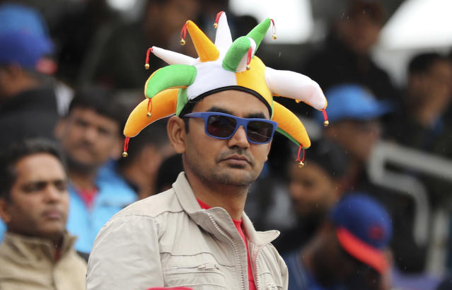 An Indian fan awaits before the Cricket World Cup semi-final match between India and New Zealand was suspended for the day due to rains at Old Trafford in Manchester, England, Tuesday, July 9, 2019. (AP Photo/Aijaz Rahi)