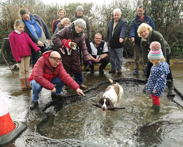Campaigners dressed up with fishing rods and swimming goggles around an enormous pothole to highlight the state of Devon's roads (SWNS)