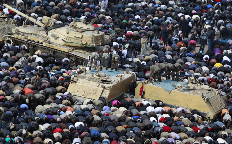 FILE - In this Feb. 11, 2011 file photo, anti-government protesters, and Egyptian soldiers on top of their vehicles, make traditional Muslim Friday prayers at the continuing demonstration in Tahrir Square in downtown Cairo, Egypt. As Egyptians mark the third anniversary of their revolution against autocrat Hosni Mubarak in the name of democracy, there has been a powerful sign of the country's stunning reversals since: letters of despair by some of the prominent activists who helped lead the uprising, leaked from the prisons where they are now jailed. The letters show a daunted and broken spirit, no longer speaking of imminent democracy, but of injustices and a failed struggle.(AP Photo/Ben Curtis, File)