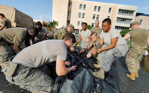 secure a portable tent as they break down a field hospital outside the Schneider Regional Medical Center while preparing to evacuate their unit in advance of Hurricane Maria - Credit: JONATHAN DRAKE/Reuters