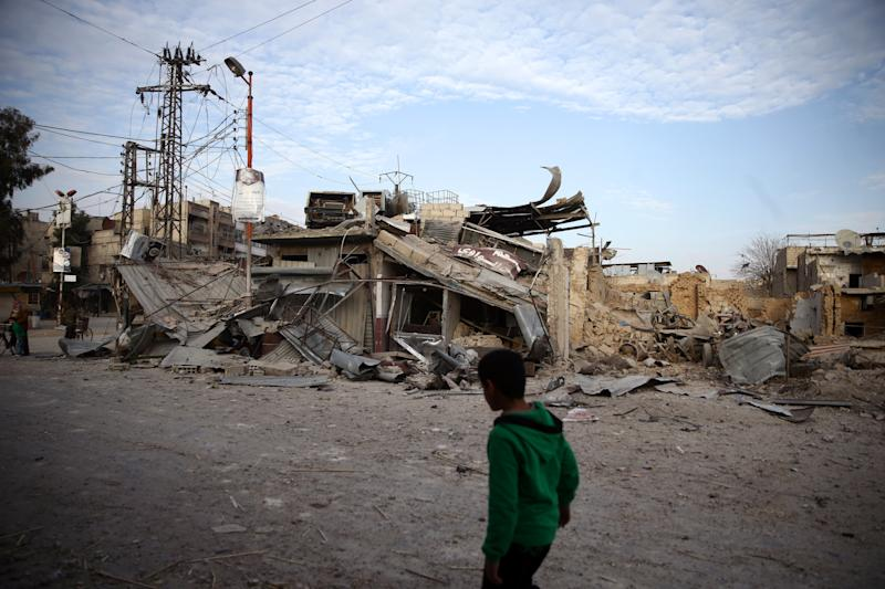 A child walks near damaged buildings in the besieged town of Douma, Syria, on Feb. 20, 2018. (Bassam Khabieh / Reuters)
