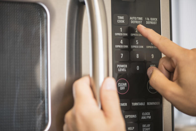A person uses a microwave.