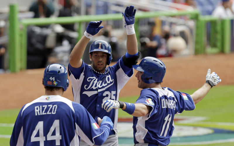 Italy's Chris Colabello (25) is congratulated at home plate by teammates Anthony Rizzo (44) and Chris Denorfia (11) after Colabello hit a three-run home run against the Dominican Republic in the first inning of the World Baseball Classic game in Miami, Tuesday, March 12, 2013. (AP Photo/Alan Diaz)