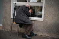 Javier Anto, 90, prays in front of his wife Carmen Panzano, 92, through the window separating the nursing home from the street in Barcelona, Spain, Wednesday, April 21, 2021. Since the pandemic struck, a glass pane has separated _ and united _ Javier and Carmen for the first prolonged period of their six-decade marriage. Anto has made coming to the street-level window that looks into the nursing home where his wife, since it was closed to visits when COVID-19 struck Spain last spring. (AP Photo/Emilio Morenatti)