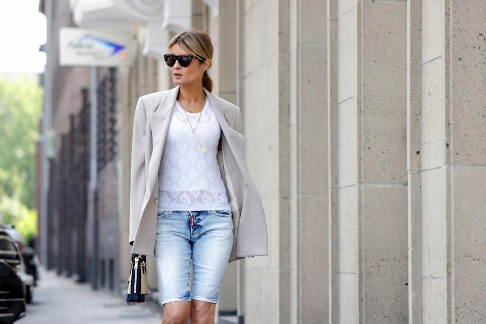 DUSSELDORF, GERMANY - JUNE 02: Influencer Gitta Banko wearing a beige oversized linen blazer by Zara, a white pullover with lace detail by Boscana, light blue denim jeans bermuda pants by Bottega Veneta and a black and beige bag with gold details by Gucci during a street style shooting on June 2, 2021 in Dusseldorf, Germany. (Photo by Streetstyleshooters/Getty Images)