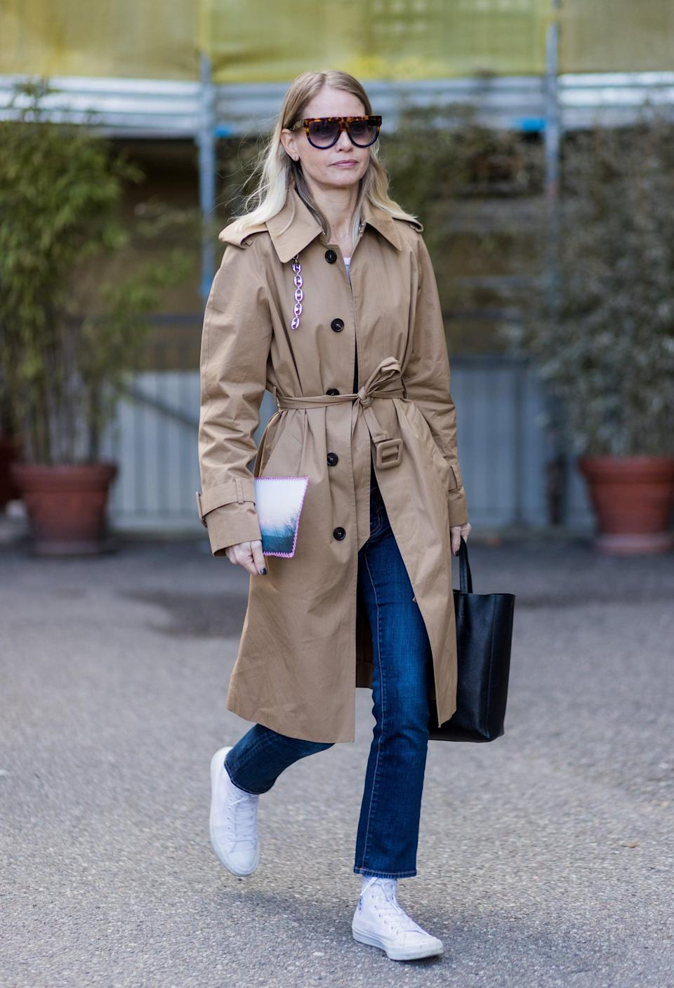 <p>A classic combination, slim straight-leg jeans appear polished with fitted high-tops and a belted trench.</p>