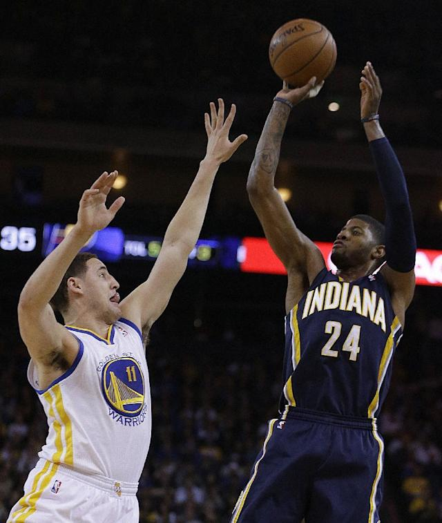 Indiana Pacers' Paul George, right, shoots over Golden State Warriors' Klay Thompson (11) during the first half of an NBA basketball game, Monday, Jan. 20, 2014, in Oakland, Calif. (AP Photo/Ben Margot)